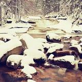 Inverno al fiume della montagna Grandi pietre in corrente coperta di neve fresca della polvere e di acqua pigra con a basso livel Fotografia Stock