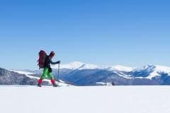 Inverno che fa un'escursione nelle montagne sulle racchette da neve con uno zaino e una tenda Fotografia Stock