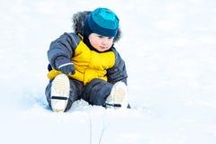 inverno, a criança feliz rola para baixo um monte da neve sobre o fundo natural fotografia de stock royalty free