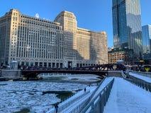 inverno de Chicago que caracteriza o riverwalk coberto de neve, os pedaços do gelo no rio e os assinantes empacotados acima fotografia de stock