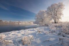 Inverno do russo Neve e geada branca de Frosty Winter Landscape With Dazzling da manhã, rio e céu azul saturado imagens de stock royalty free