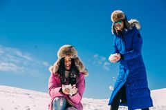 Inverno, due ragazze divertendosi nella neve nelle montagne Fotografia Stock Libera da Diritti