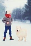 inverno e conceito dos povos - menino com o cão branco do Samoyed Imagens de Stock Royalty Free