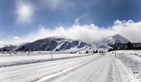inverno e neve na estrada que conduz às montanhas imagem de stock