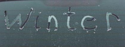 inverno escrito à mão da inscrição na janela de vidro da parte traseira do carro do gelo Foto de Stock