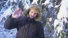 inverno Forest Traveler With Backpack Acenando sua mão na câmera Manhã ensolarada bonita na floresta do inverno video estoque