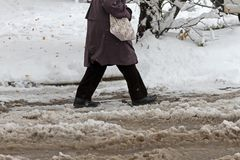 Inverno Gelo neve O pessoa anda duramente em uma estrada gelada nevado que passa carros nevado em rua gelada uncleaned após uma q imagens de stock