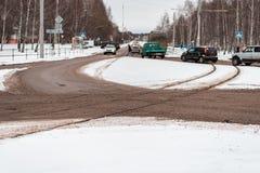 inverno na cidade do cruzamento pedestre da zebra Carros e bondes na cidade Os traços sujos da neve da estrada transportam linhas Imagens de Stock Royalty Free