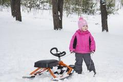 Inverno nella guida della bambina della foresta sui neve-gatti Immagine Stock