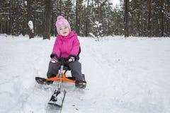 Inverno nella guida della bambina della foresta sui neve-gatti Immagine Stock Libera da Diritti