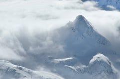 Inverno nelle alpi con le nuvole sopra le montagne Fotografia Stock Libera da Diritti
