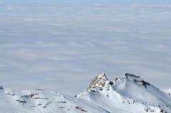 Inverno nelle alpi con le nuvole sopra le montagne Immagine Stock