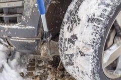 inverno, neve, carro Um homem limpa o carro da neve e o gelo com uma escova especial fotografia de stock