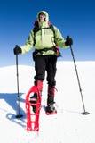inverno que caminha nas montanhas em sapatos de neve com uma trouxa e uma barraca Foto de Stock