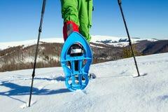 inverno que caminha nas montanhas em sapatos de neve com uma trouxa e uma barraca Fotografia de Stock Royalty Free
