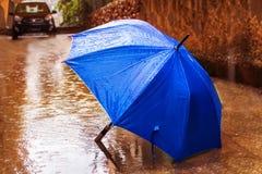inverno, tempo em Israel Chuva, guarda-chuva na poça formada, círculos na água e pingos de chuva foto de stock royalty free