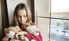Inverno triste dell'orsacchiotto della finestra della ragazza Fotografia Stock Libera da Diritti