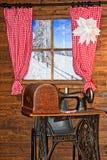 Inverno Uma casa de madeira Janela com cortinas vermelhas Fotos de Stock Royalty Free