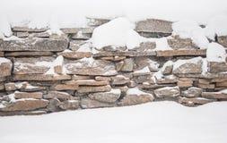 Inverno in villaggio, recinto di pietra coperto da neve fotografia stock