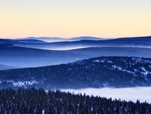 Inverse weather in mountains, shinning fog. Misty valley in winter. Mountains. Peaks of mountains above creamy mist stock photography