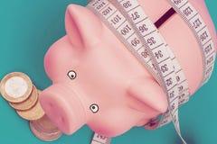 Inversiones y medici?n o cuenta de idea Cerdo de cer?mica del juguete con la regla flexible blanca en fondo azul Dieta financiera fotos de archivo