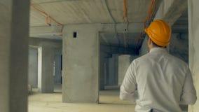 Inversor que examina el edificio Hombre de negocios en casco dentro del progreso de examen de la construcción del emplazamiento d almacen de video