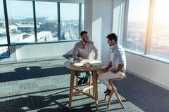 Inversores del negocio que discuten el negocio que se sienta en la tabla en offic foto de archivo libre de regalías