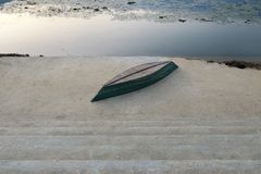An inverted boat on a concrete embankment Royalty Free Stock Photos