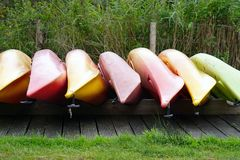 Inverted canoe boats. Multicolored inverted canoes on the shore. Multicolored inverted canoe boats stock photo