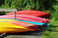 Inverted canoe boats. Multicolored inverted canoes on the shore. Multicolored inverted canoe boats royalty free stock photos