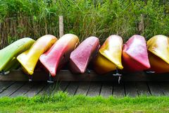 Inverted canoe boats. Multicolored inverted canoe boats. Multicolored inverted canoes on the shore stock photos