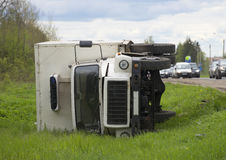Inverted cargo van-refrigerated truck lies in a ditch Stock Photo