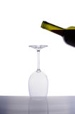 Inverted empty wine glass and bottle of red wine Royalty Free Stock Photography