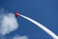 Inverted Roll. A stunt airplane performs a inverted roll at an airshow. Bright blue sky royalty free stock images