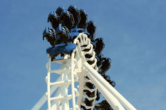 Inverted Roller Coaster. The top loop of an inverted roller coaster with a white track and an empty train of blue seats flying around the top of it, against a stock photos