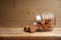 Inverted sheer jar with chocolate cookies in the shape of heart. Inverted ribbed sheer jar with many chocolate cookies in the shape of heart Stock Photos