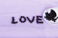 Inverted white cup with black currants with an inscription Royalty Free Stock Photo