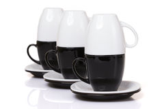 Inverted white cups stands on black cups with stack plates. Stock Photography