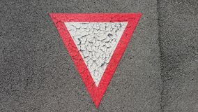 Inverted white with red border triangular road sign yield that you need to wait stock photos