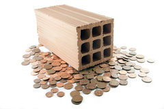 Invest in bricks and mortar. Brick standing on disorderly spilled euro coins royalty free stock photography