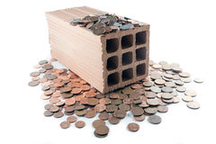Invest in bricks and mortar. Brick standing on disorderly spilled euro coins royalty free stock image