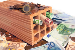 Invest in bricks and mortar. Brick standing on disorderly spilled euro coins stock photos