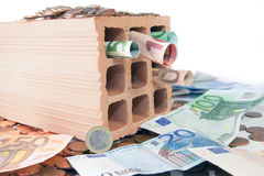 Invest in bricks and mortar. Brick standing on disorderly spilled euro coins stock images