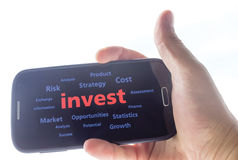 Invest. Concept background ,hand holding a smart phone Stock Photography