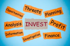 Invest concept. Word on torn paper color on blue background. business concept Royalty Free Stock Photos