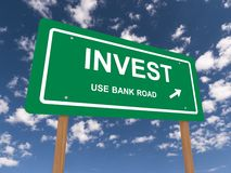 Invest green sign against blue sky Stock Photos