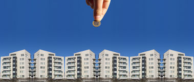 Invest in Real Estate. A hand holds a coin over an image of an apartment or condominium complex, suggesting investment in real estate stock photography