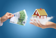 Invest in real estate. Concept of home ownership. Hands with money. New house in other hand Stock Image