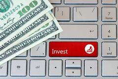 Invest Red Button on laptop keyboard with dollar banknotes. Closeup View royalty free stock images