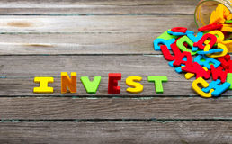 Invest. Text on wood background Royalty Free Stock Images